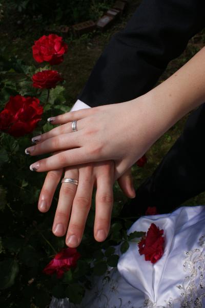 Die Hände eines Brautpaares mit Trau-Ringen und Rosen im Hintergrund