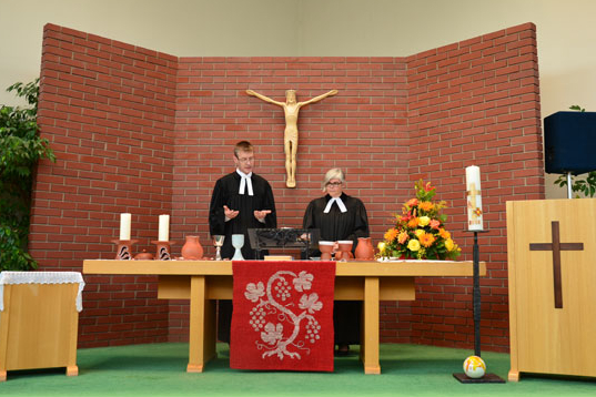 Pfarrer Andreas Carrara und Pfarrerin Danielle Carrara stehen hinter dem Altar und bereiten das Abendmahl vor.