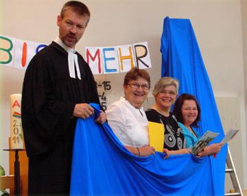 Pfarrer und Mitarbeiter halten ein blaues Tuch im Familiengottesdienst, dahinter der Schriftzug Du bist mehr