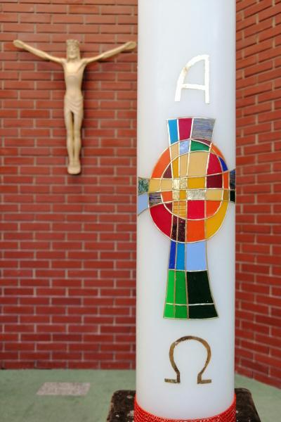 Osterkerze im Fordergrund mit Alpha, Omega und einem regenbogenfarbenen Kreuz, im Hintergrund der segnende Jesus an der Altarwand.