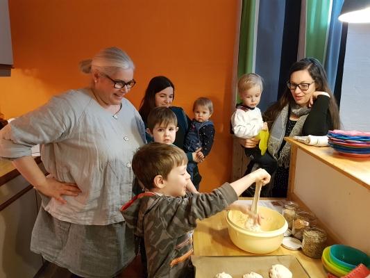 Kinder bei der Teigzubereitung gemeinsam mit KindergottesdienstMitarbeiter und einer Mutter