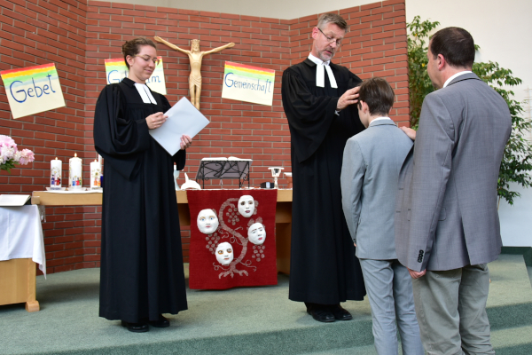 Pfarrer segnet Konfirmanden. Der Pate legt die Hand auf die Schulter des Konfirmanden.