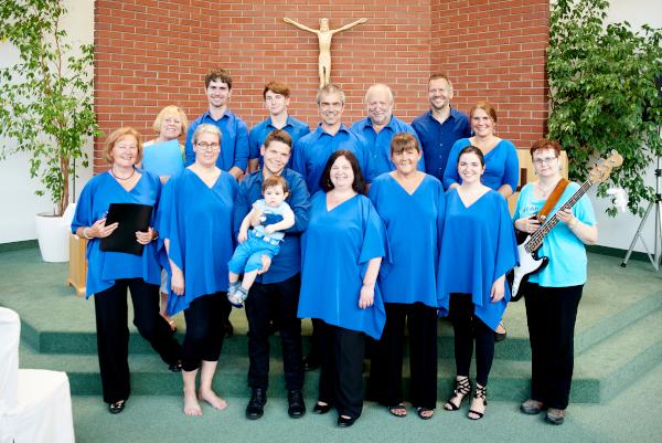 Gospelchor, Gruppe von Sängern in blau gekleidet. Bassistin mit Bassgitarre