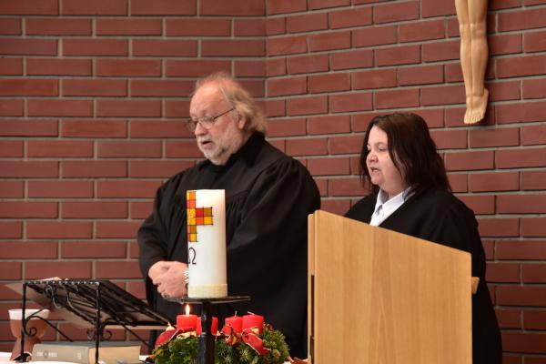 Lektor Ronald Schulz und Lektorin Claudia Buchner stehen hinter dem Altar