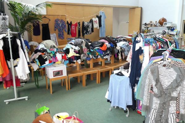 Kleidungsstücke auf Kleiderständern im Kirchenraum