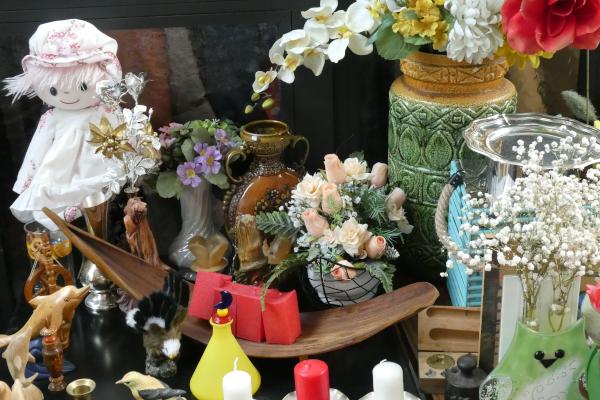 Flohmarktwaren, wie Puppen, Kunstblumen und Schmuck.