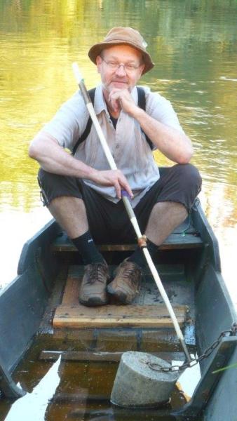 Pfarrer Andreas Carrara sitzt in einem Ruderboot auf einem See.