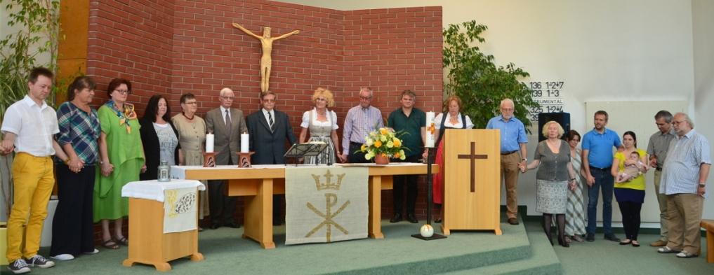 Gemeindevertreter stehen Händehaltent um den Altar